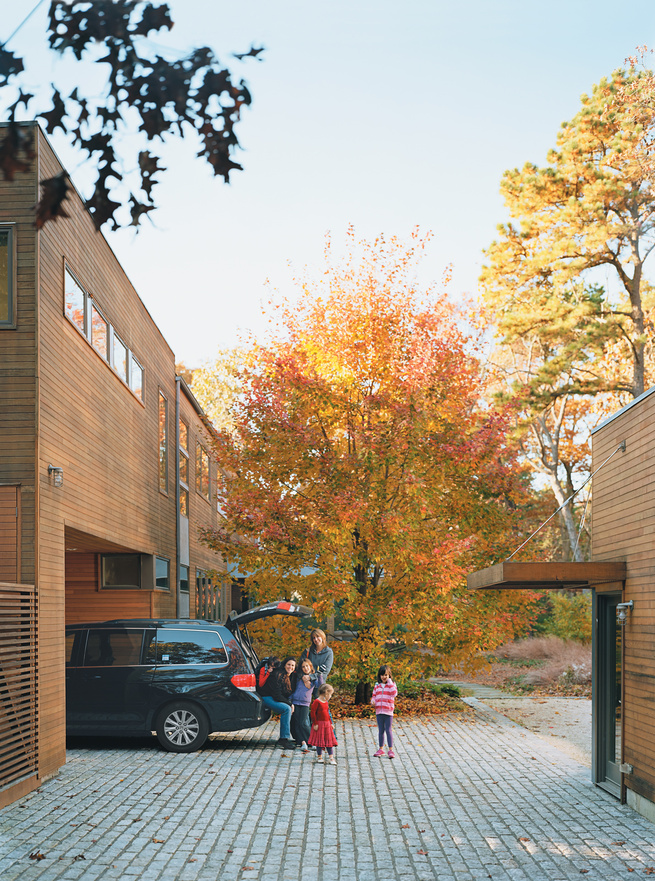 The house was deliberately sited to preserve the two-acre property's existing trees, three of which can be seen protruding through the surface of a rear deck.