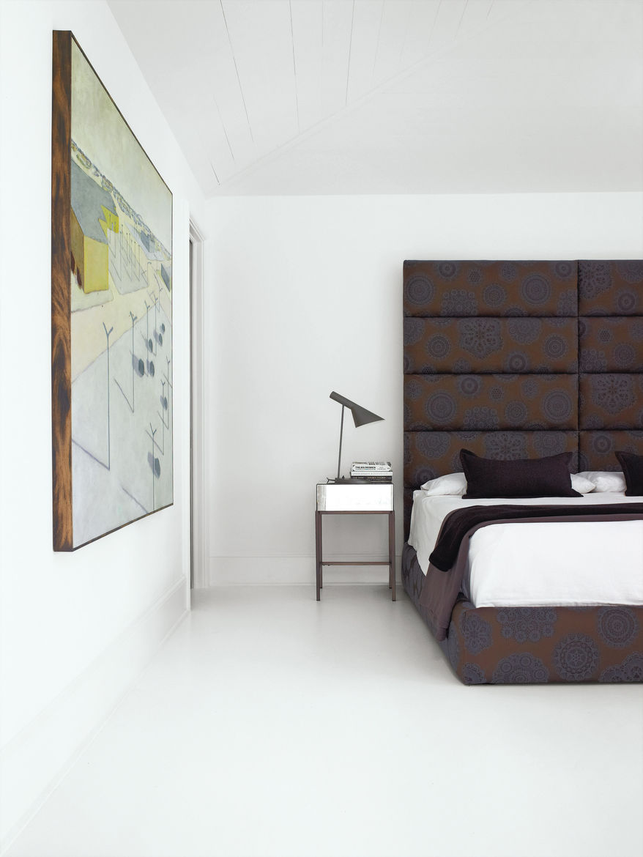 Minimalist bedroom with tall headboard and Maharam fabric