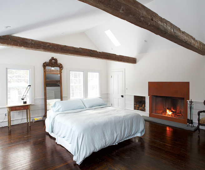 Master bedroom wooden beams gas fireplace Artemide lamp