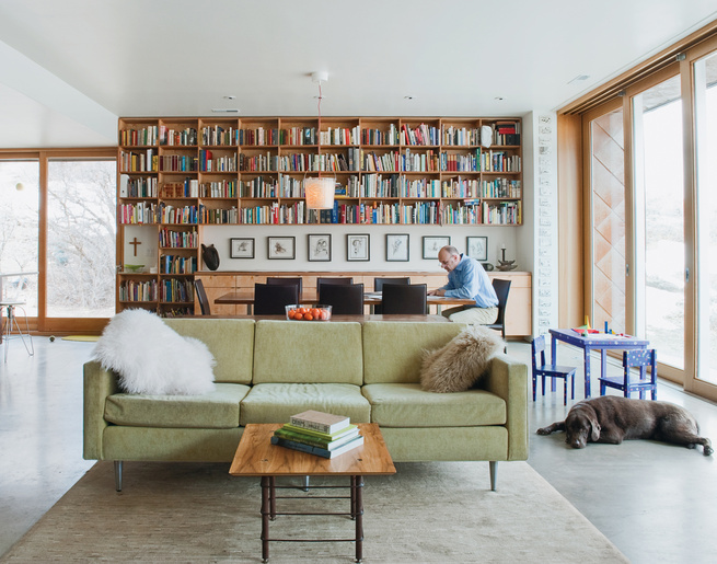 Sparano works in the dining area, where books about travel, architecture, and food, as well as framed architectural drawings from his grad school days, line the back wall. The hollow glass-walled light fixture is from Ikea; every few months, the family fi