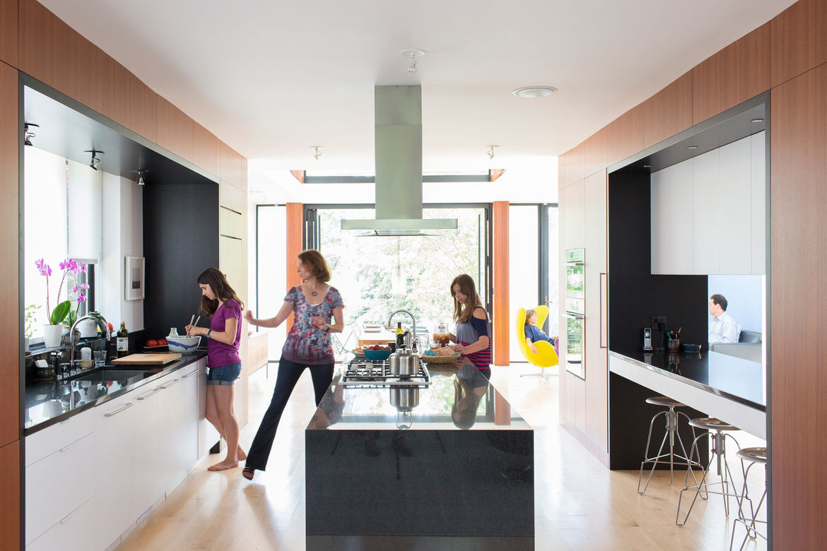 Modern kitchen design with hardwood floors, island, and black countertops