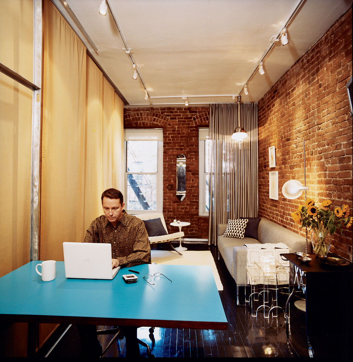 Checking email over coffee, Hughston places his laptop on the fold-down Formica table that Sanders designed. Jack Lenor Larsen's Cybelle fabric covers the wall on his right. Above the sofa hangs an Italian pendant lamp of mysterious origin; if you recogni