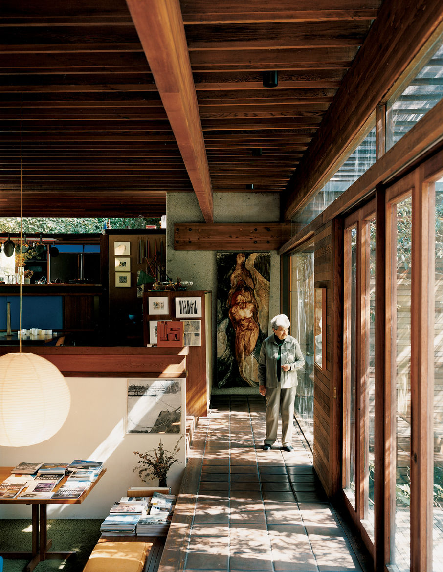 """Shelly walks along the perimeter of the house, near the central living area. The design of the house, with its many rooms, nooks, and open family spaces, """"was so ahead of its time,"""" Shelly says, """"that, to young people coming here, it still feels contempor"""