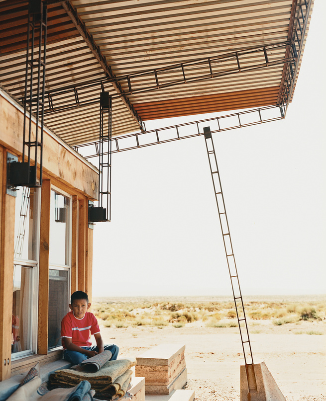 Nicholas sits in the shade of the roof; students cut and hand-welded thousands of reclaimed rebar pieces into a complex grid that would support four bi-level  corrugated-steel roof panels.