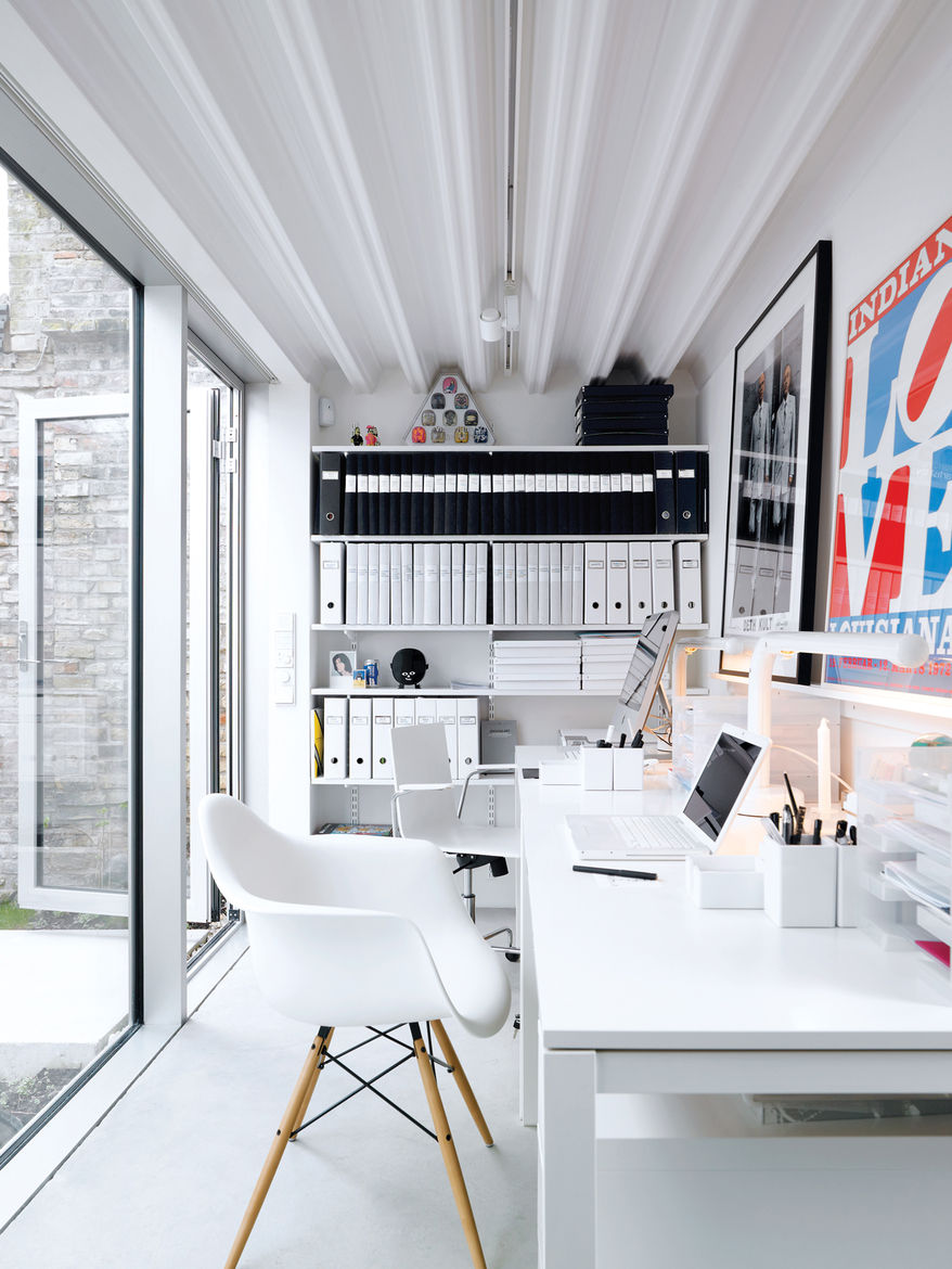 The office, which is a single-level separate unit, boasts Ikea desks and a signed work by Gilbert and George (friends of the couple).