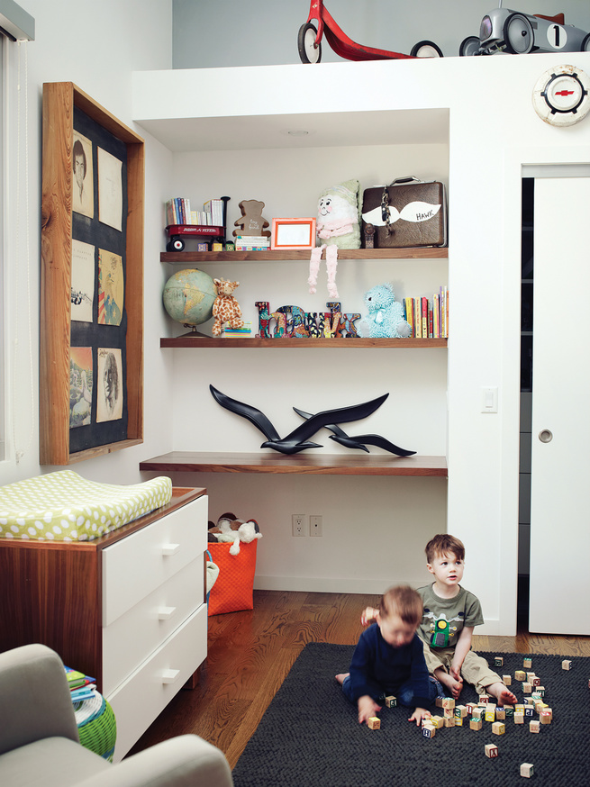 Modern kids room with built-in shelves and Ducduc changing table