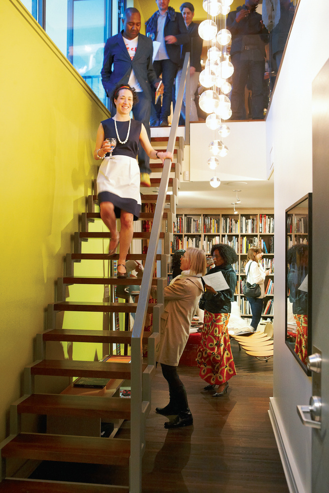 Modern staircase area with yellow wall and bubble chandelier