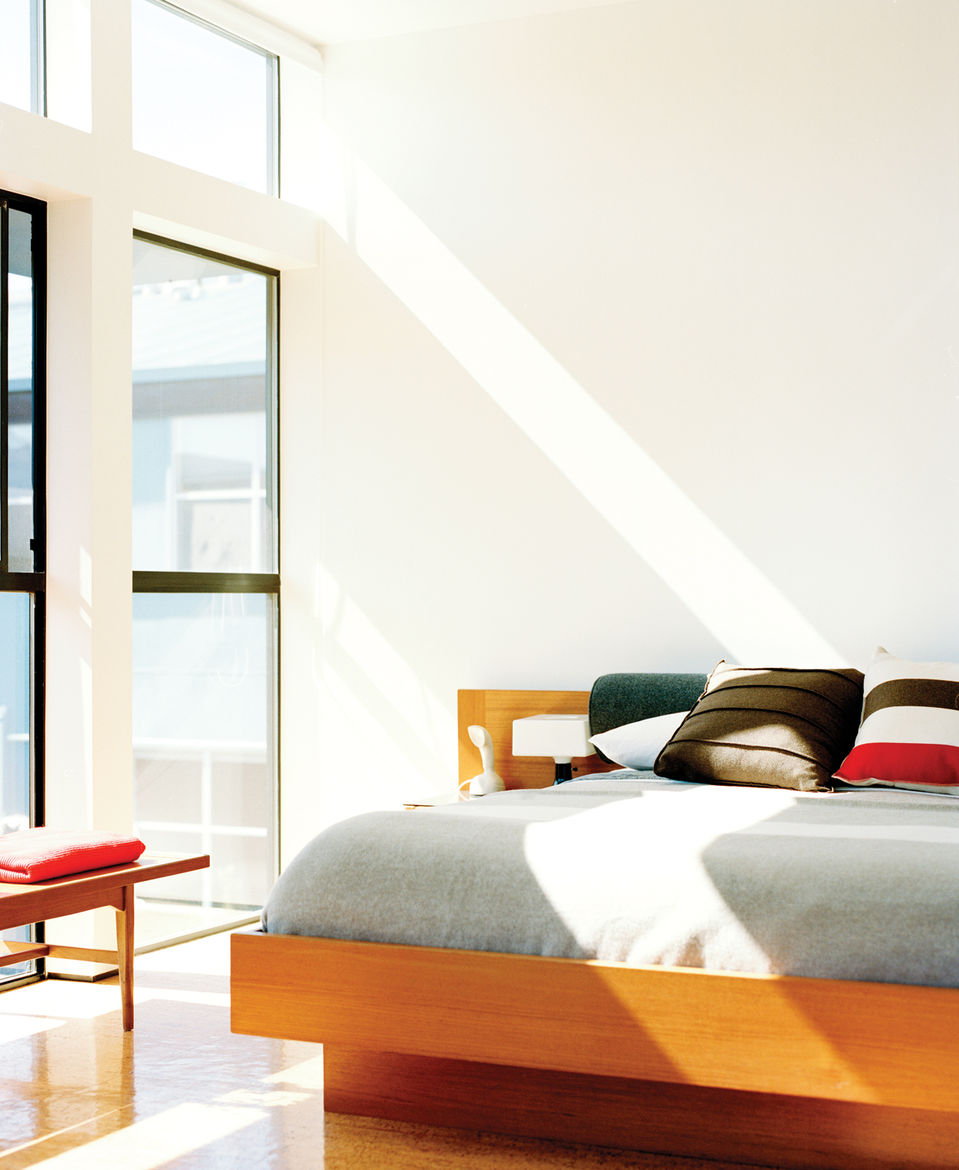 Light-filled bedroom with Danish floating bed and vintage teak coffee table