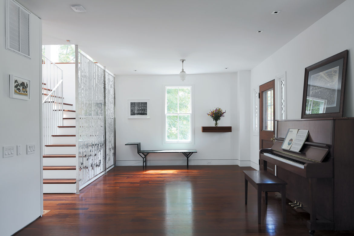 Modern foyer with family piano and Jean Prouve bench