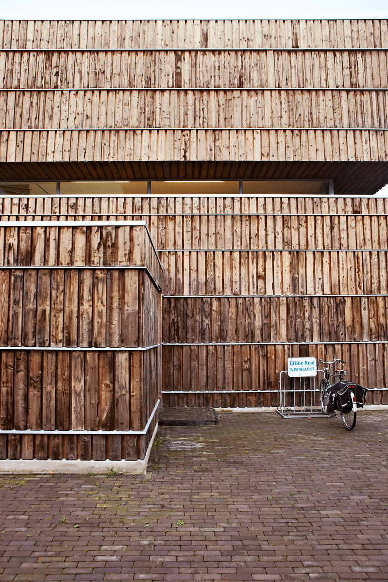 Facade clad with wood and recycled cable reels