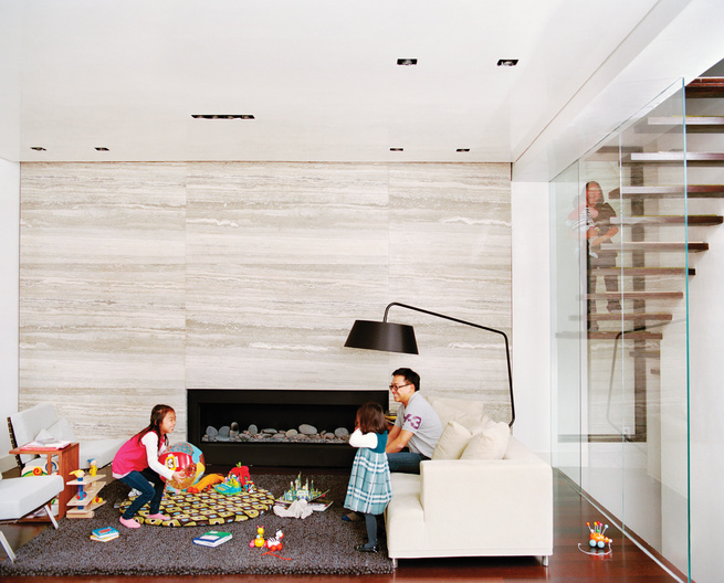 Double-height living room with silver travertine marble slabbed wall