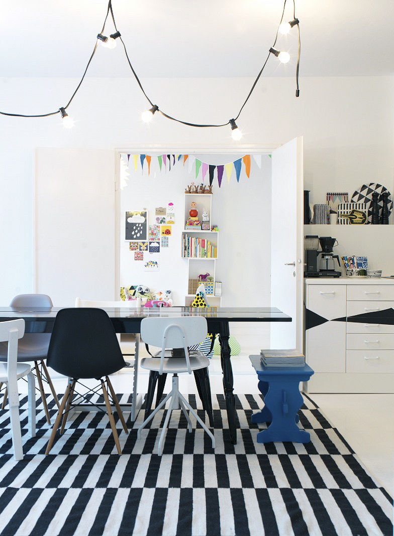 Modern open-plan dining room with various chairs and striped rug