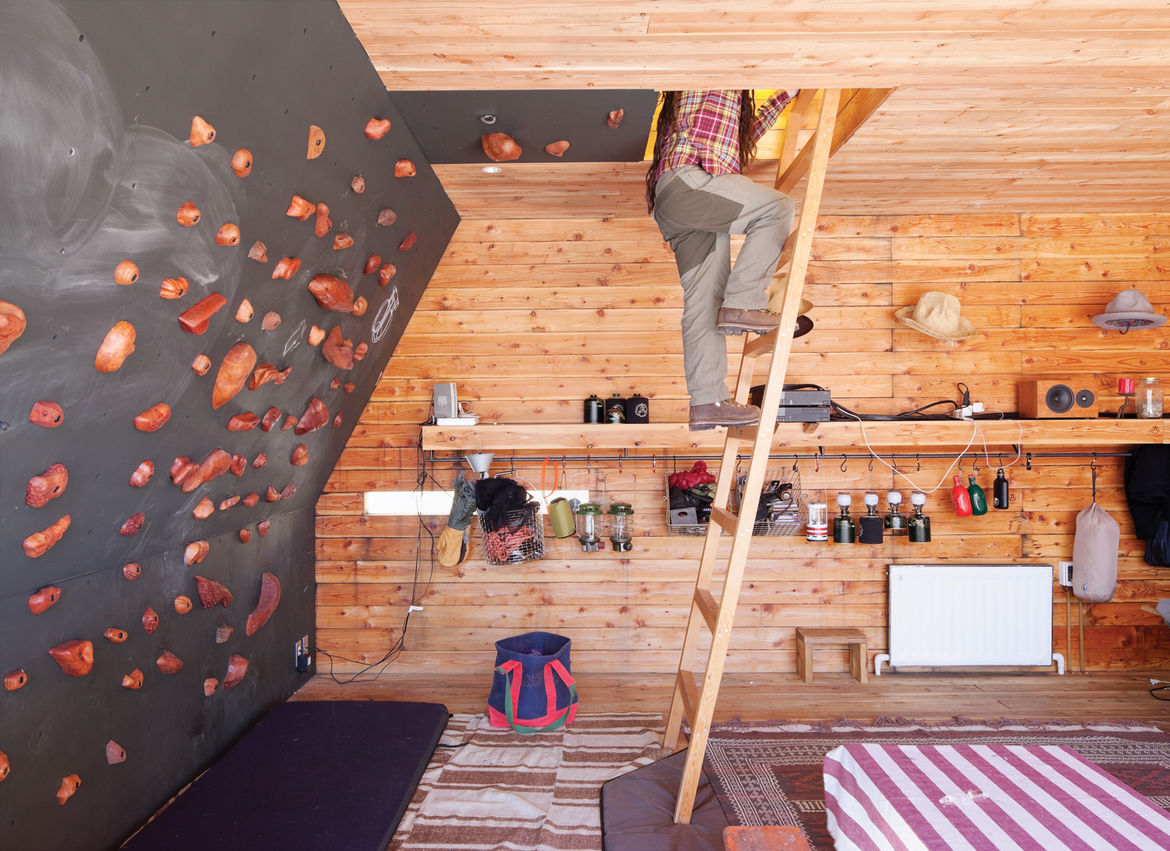 Wood house interior with wood ladder leading to rooftop tent