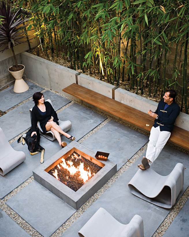 Backyard fireplace area with a long steel-and-ipe bench and Willy Guhl Loop chairs