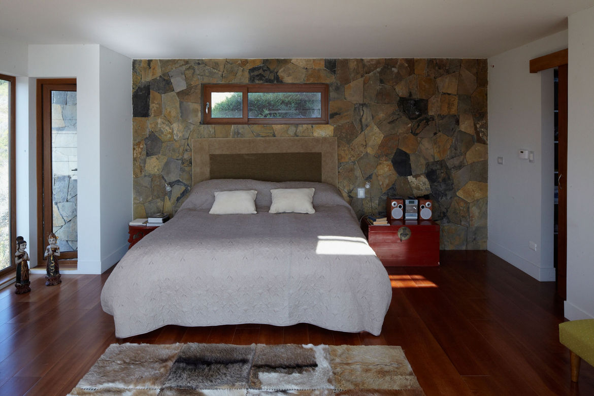 Lower level bedroom with bed behind thermal-mass wall