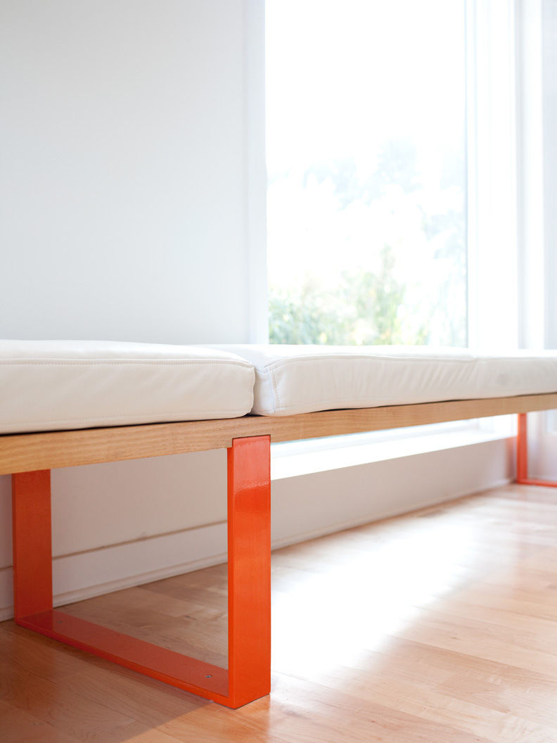 Padded steel-and-metal bench with orange legs in living room