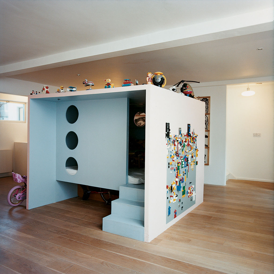 Danish furniture and product designer Nina Tolstrup, who works under the name Studiomama, conceived a huge, freestanding medium-density fiberboard (MDF) cube punctured with circular windows that acts as her children's playroom inside her London home. <a h