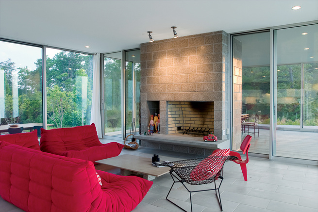 modern living room with red furniture and concrete fireplace