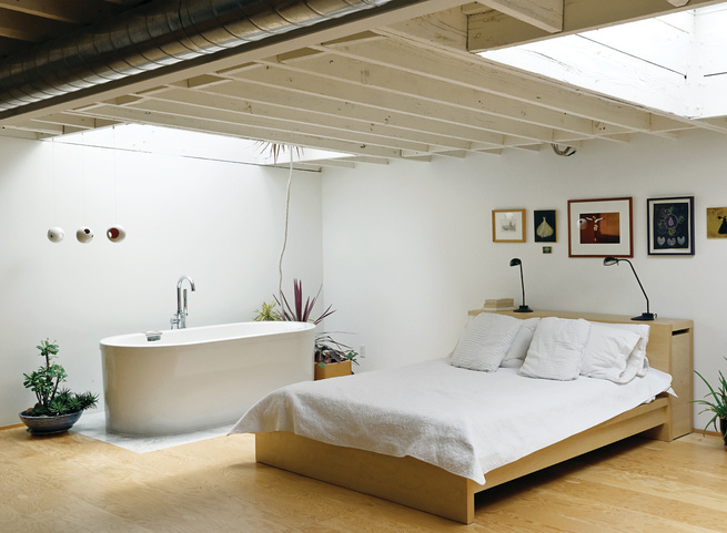 Joint bathroom and bedroom with a Neptune bathtub and wall art