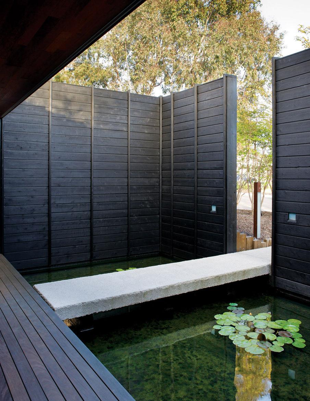 Large koi pond on a cast-concrete footbridge by entrance