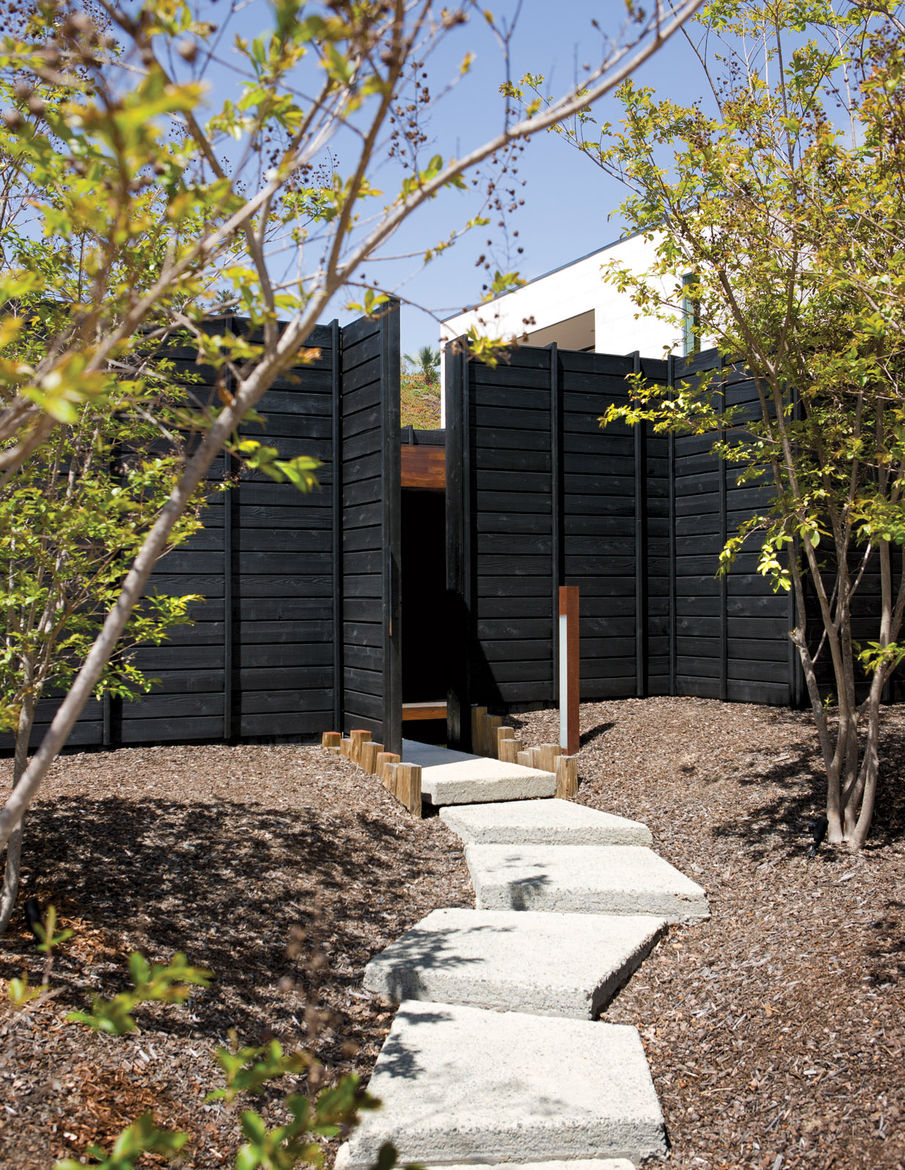 Entrance pathway with a charred cedar façade and concrete pads