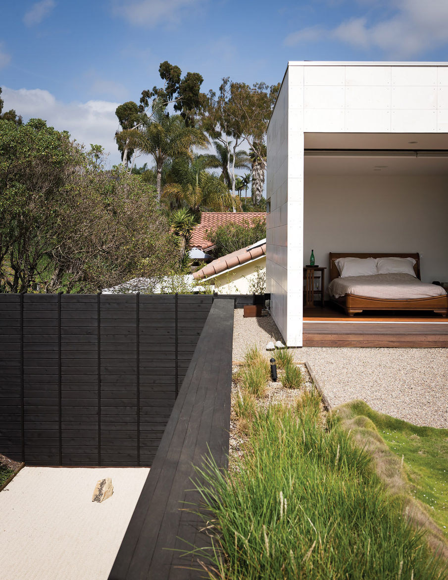 Limestone-clad volume on planted roof deck with a simple backyard