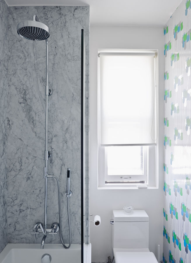 "In the bathroom, the gray Carrara walls are offset by bright tulip-patterned wallpaper, circa 1970, from Secondhand Rose in Tribeca. The toilet is a Philippe Starck ""jet action"" model from Duravit."