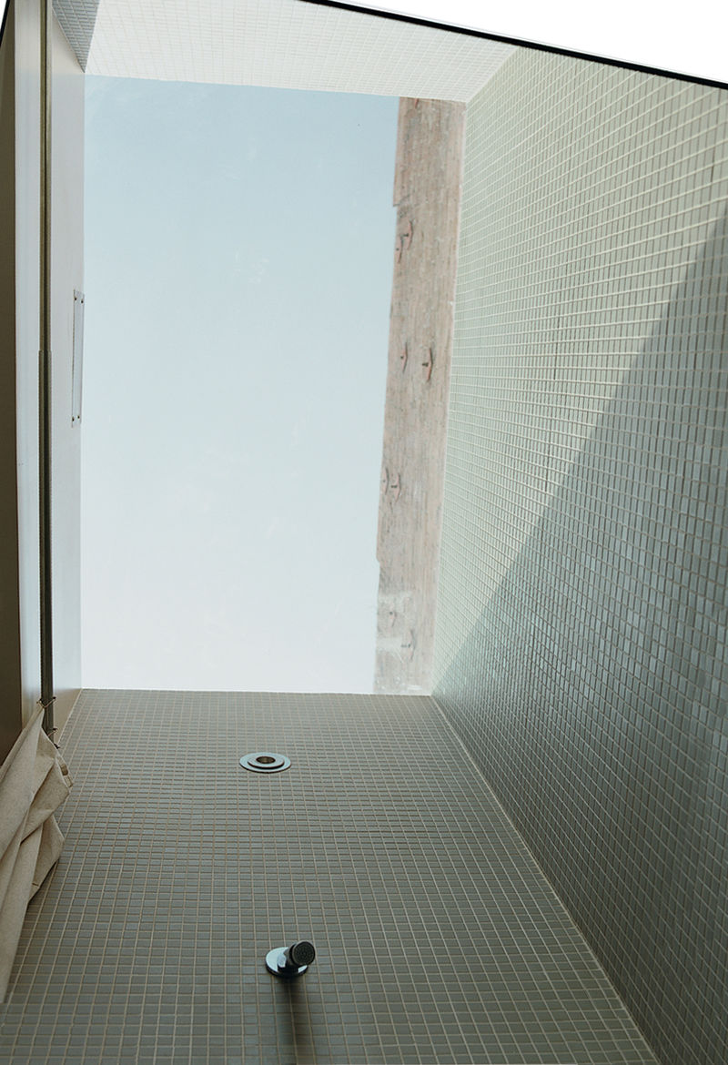 A skylight over the middle of a room is a nice thing. But, as architect Riley Pratt demonstrates, using a skylight along the edge of a room can help dematerialize walls and make an indoor space feel especially luminous. Here, a shower stall inside a renov