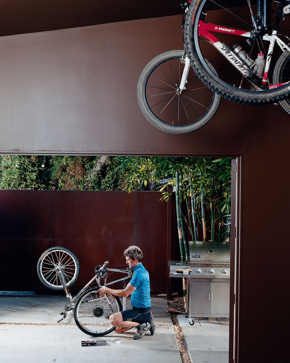 Pierre Kozely mends his bike on a patio in the rear yard, seen from their garage—which was transformed into a media room. Behind him is a Cor-Ten rolling gate that gives access  to the back alley.