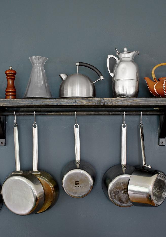 Silver kitchenware on wooden shelf