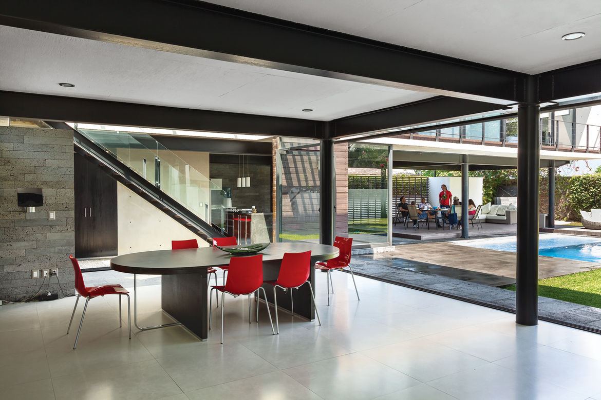 Modern dining room area with oval table and red chairs