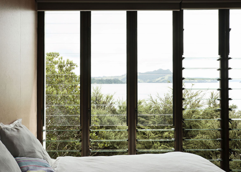 Modern bedroom with louvered windows and a view of Maramaratotara Bay