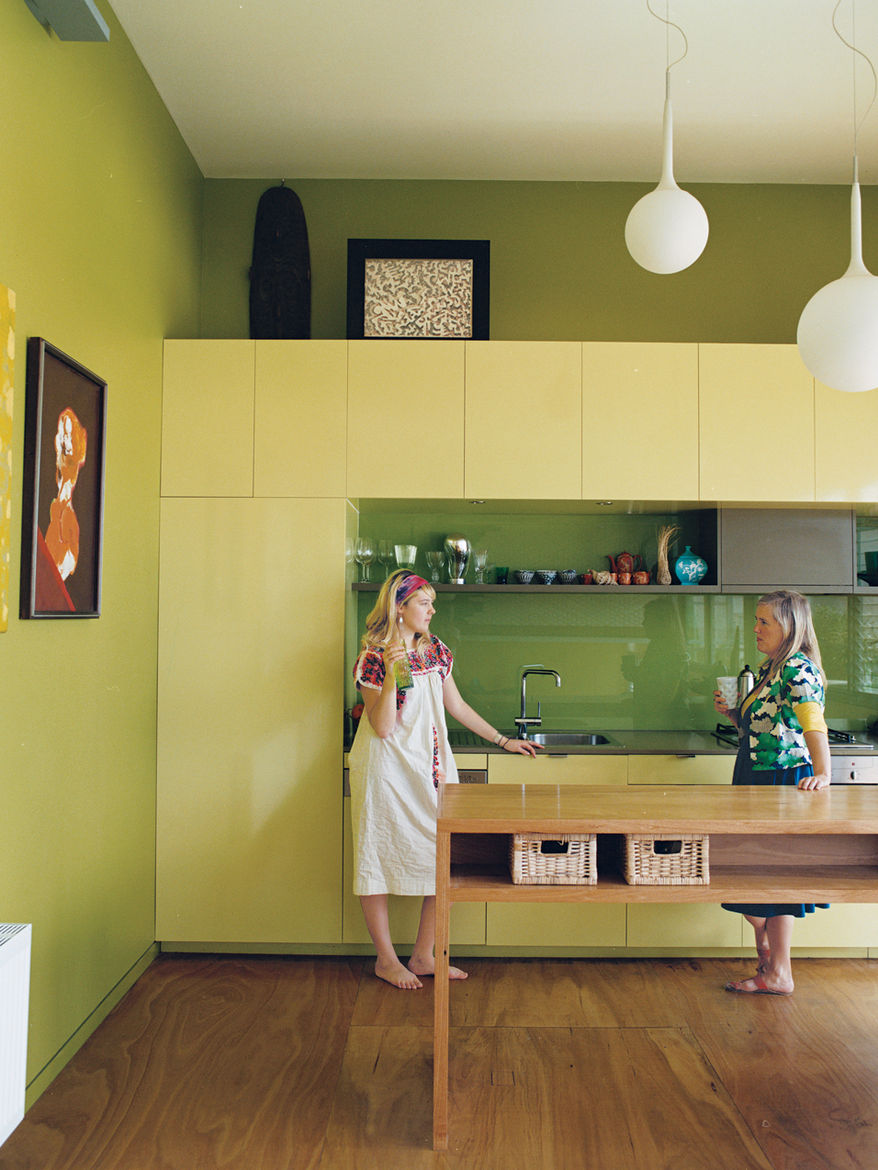 The eye-catching kitchen cabinets behind Cat Macleod and her daughter, Celeste, were custom-built in lemon Liri Laminate by Amerind. The island bench is made from the same alpine ash used on the floor and the stairs all the way up to the master bedroom. <