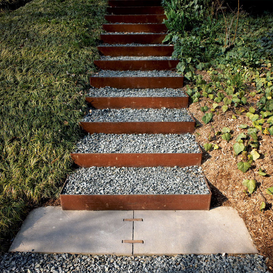The stairs going up the knoll to the roof garden and to the house's second-level entrance are made from Cor-Ten steel risers (which develop a rich, rusted patina) and filled with gravel in order to create a nonslip surface that drains well. Steel and stee