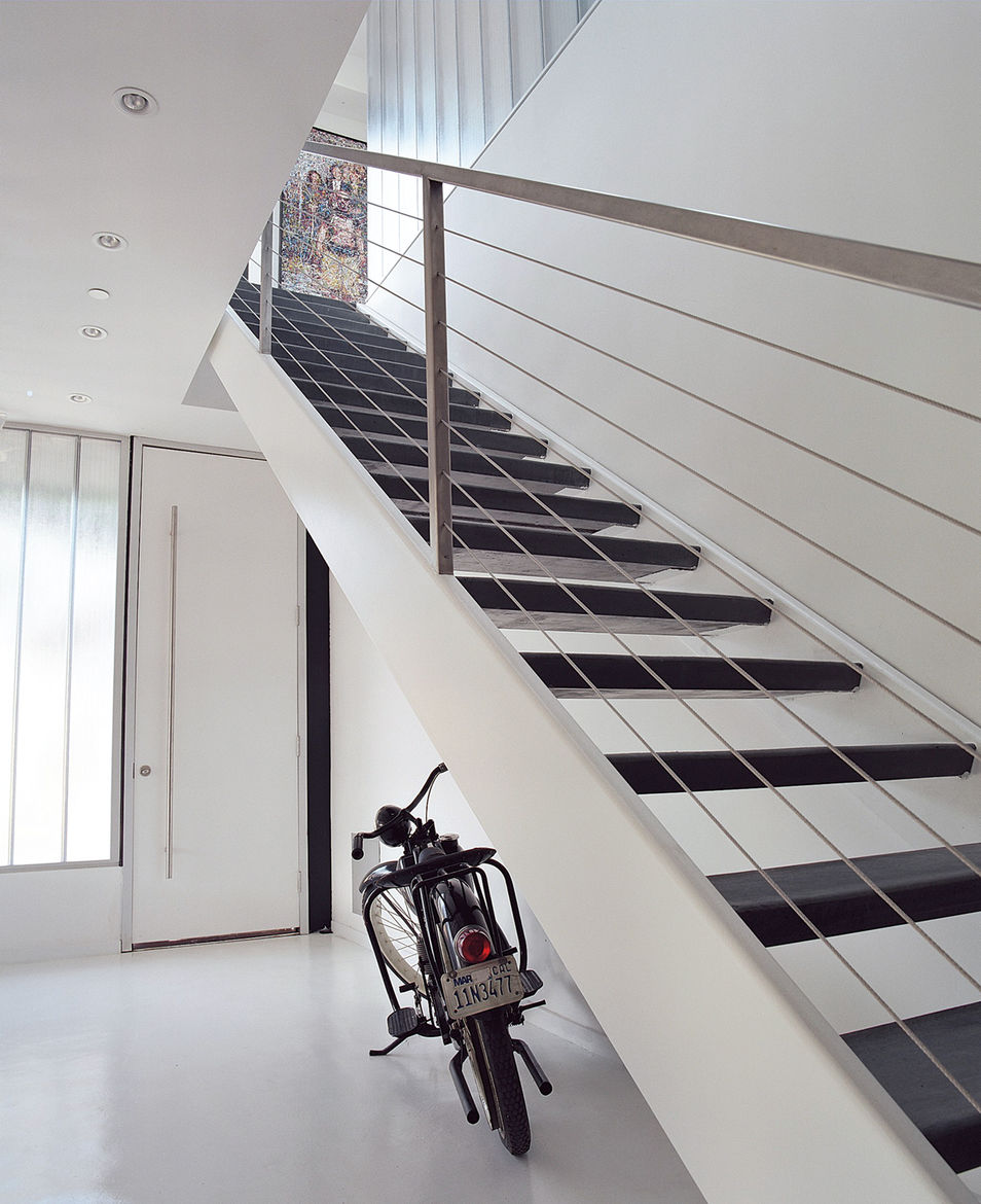 Inside Greg Reitz's Los Angeles home, the entryway features fly-ash concrete floors and stairs cut from recycled steel. Conscious of the life-cycle of the materials he chose, he settled steel instead of wood on the grounds that it would last longer and wo