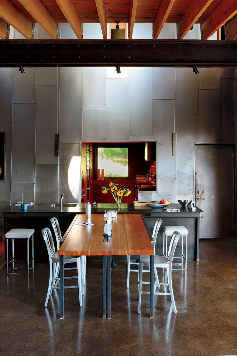"A custom recycled-Douglas fir table by VanEyk Custom Woodworks is the heart of the living-dining room in the so-called ""Scrap House."" The double-height wall is clad in the same steel that wraps the exterior. <a href=""http://www.dwell.com/articles/scrap-ho"