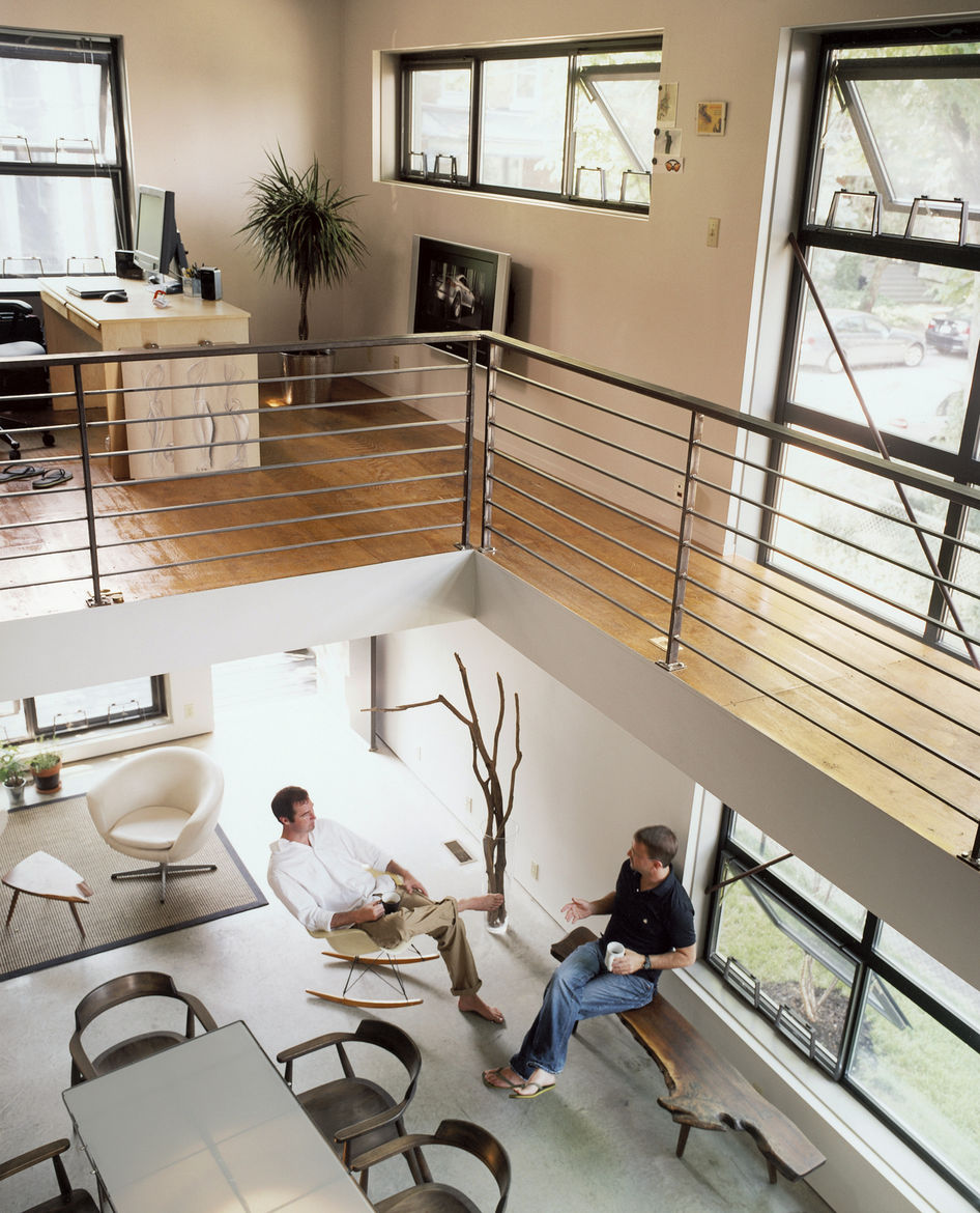 The open office and bedroom reside on either side of the second story catwalk. Below, Walz rests on a George Nakashima–inspired bench designed by architect Harry Levine's Uncle Murray, while industrial designer Scott Summitt sits in a vintage Eames rocker