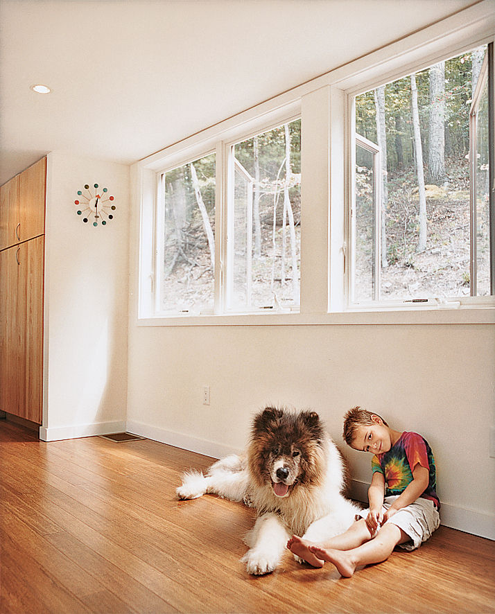 Little boy with pet dog sitting on wooden floor