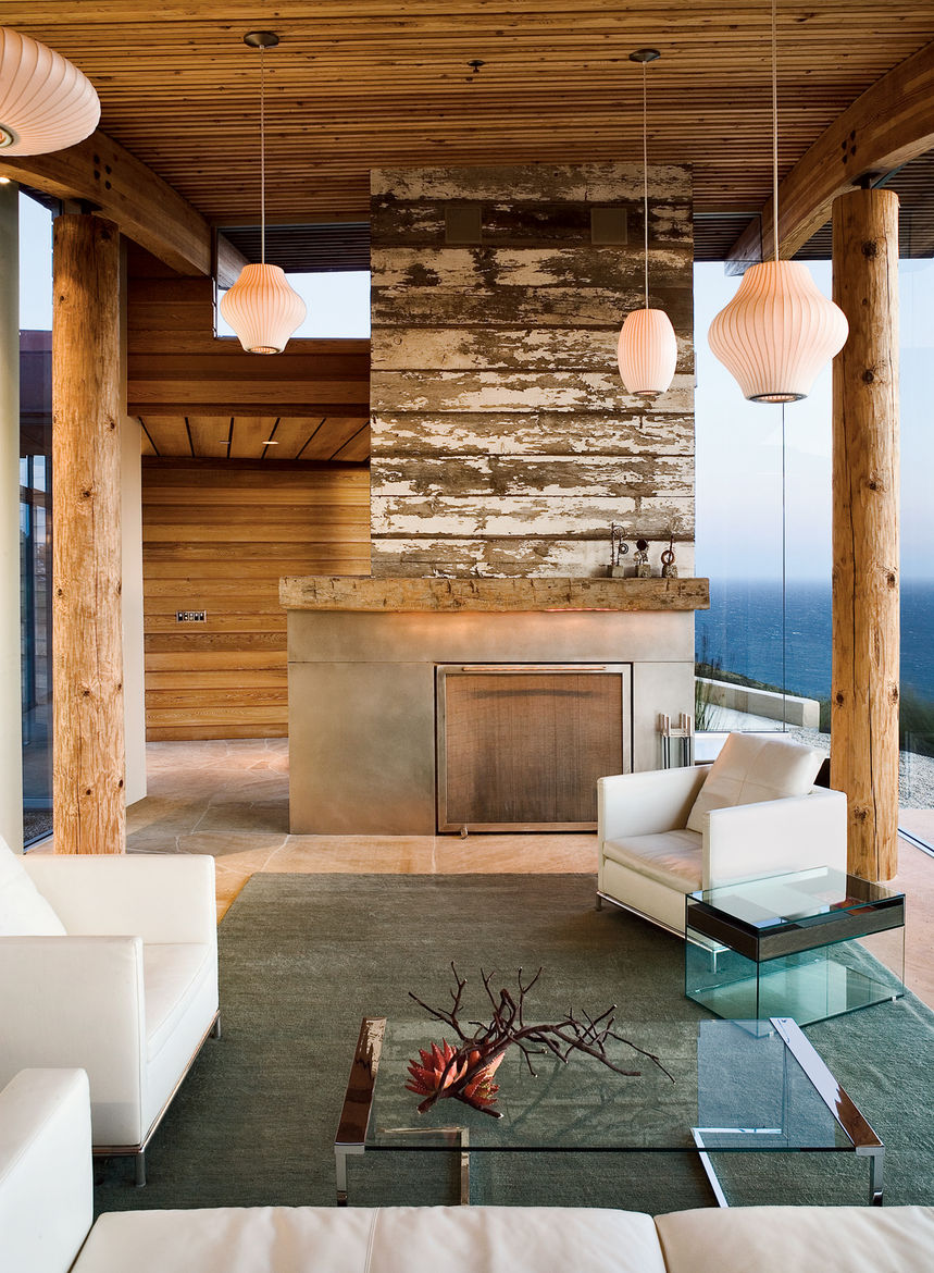 "For her home in Big Sur, California, Mary Ann Schicketanz of Carmel architecture firm Carver & Schicketanz conceived a reclaimed-wood fireplace for the living room. Additional warmth is garnered through the limestone flooring. <a href=""http://www.dwell.co"