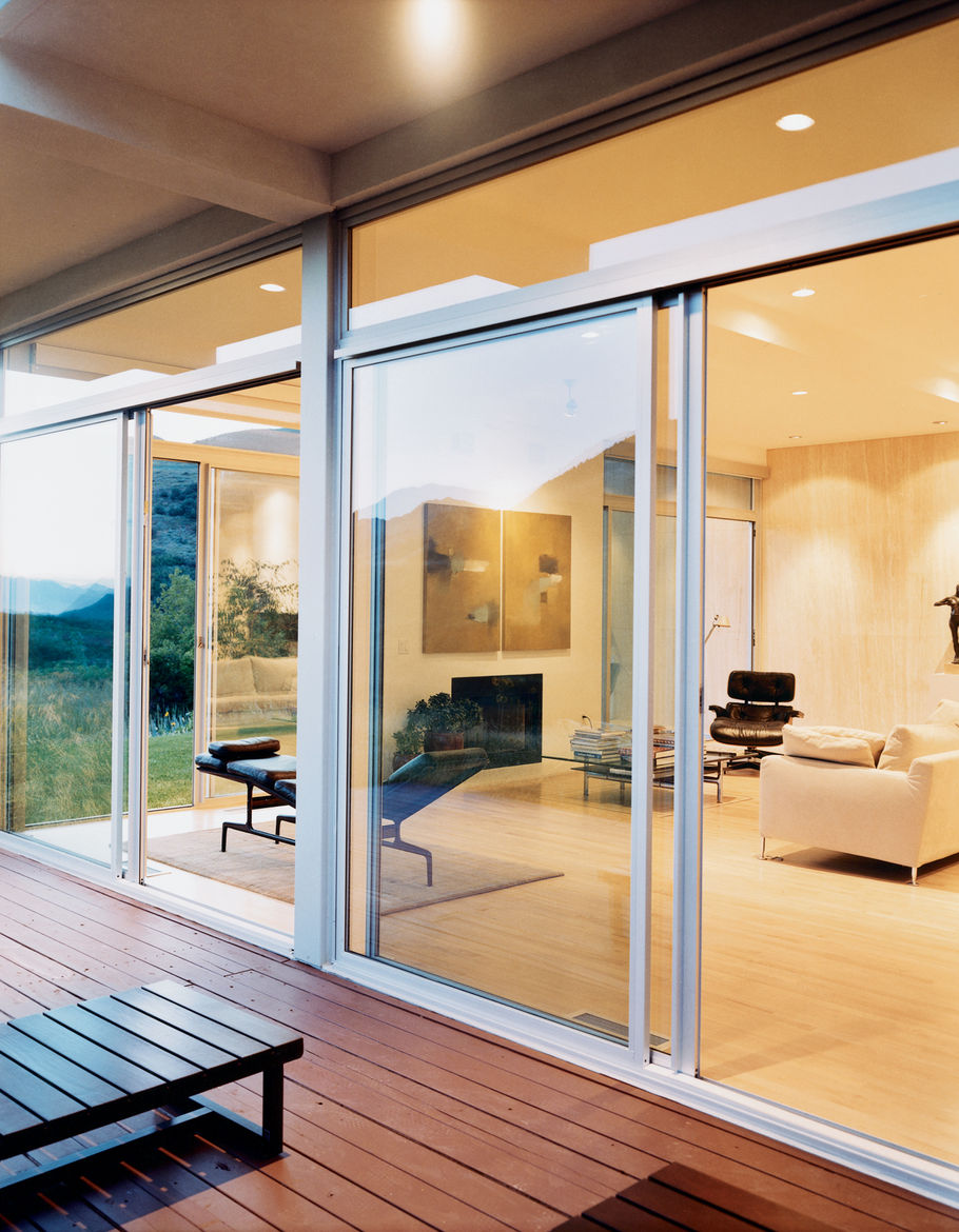 The living room utilizes Eames lounges and a B&B Italia sofa to create a spare but comfortable environment. Sliding glass doors provide ample ventilation.
