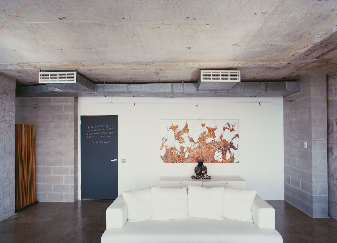 The words of the prophets are written on the chalkboard-paint-coated door to Hill's apartment. A painting by Mark Flood hangs behind a plaster Buddha on a chest from Cassina. The Ligne Roset cotten sofa was bought on sale.