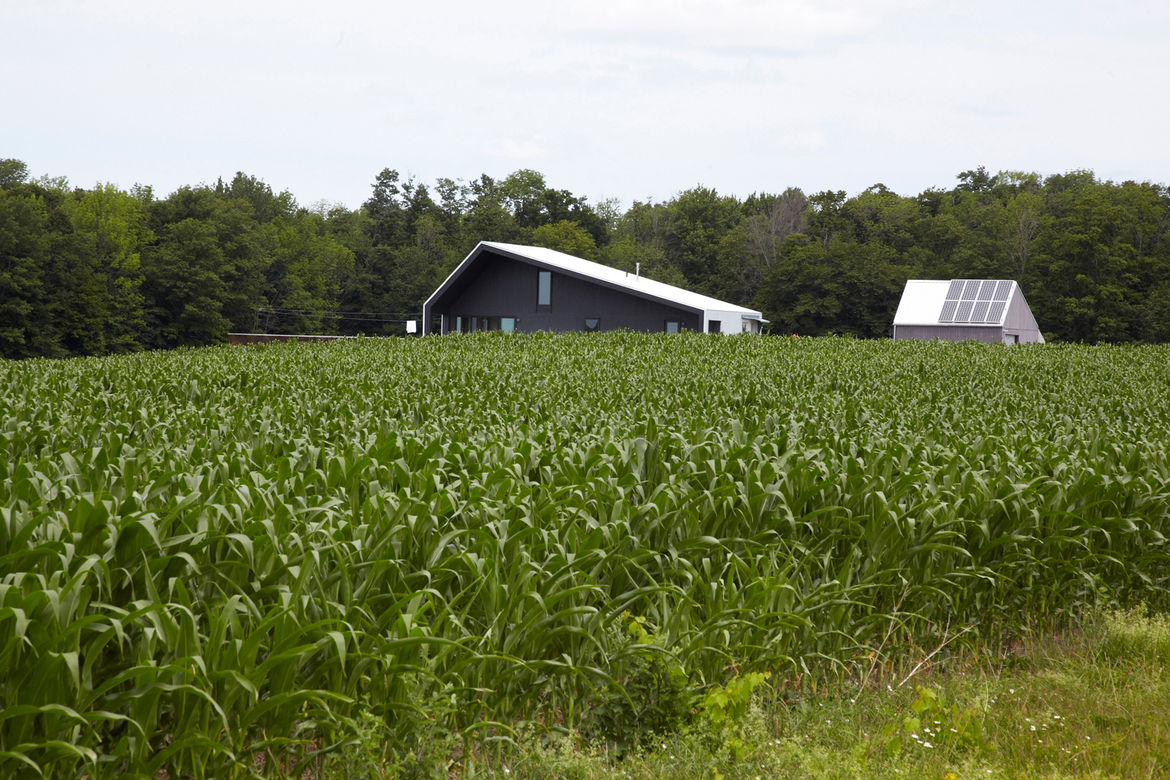 Field view of modern off-the-grid house with solar panels