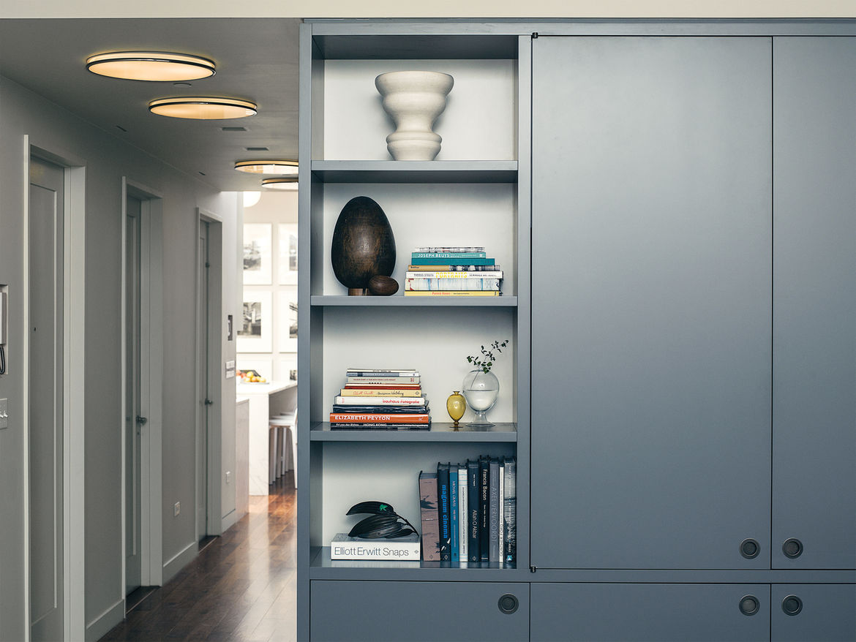 Living room bookshelves with various glassworks.