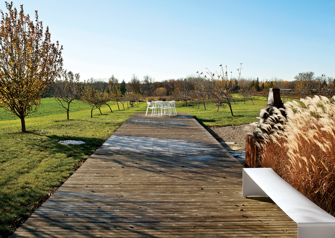 Wooden decking with white bench, chairs, and table