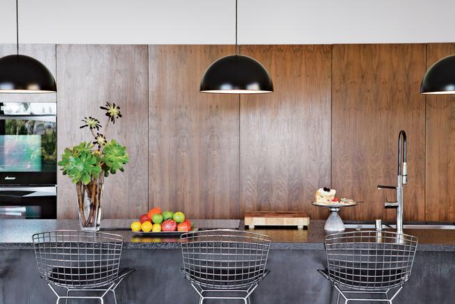 Black pendant lambs hang over countertop and metal tall chairs