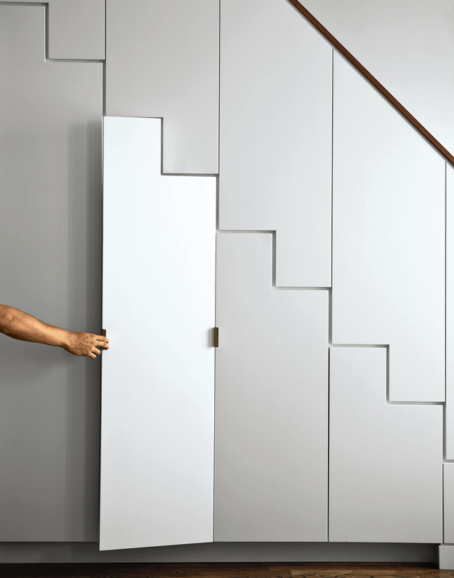 Hidden storage stairwell with raw brass hardware