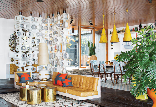 a sculptural room divider of white and grey separates a white couch with orange cushions from a dining room with dark wood chairs covered in cloth with white and blue geometric patterns