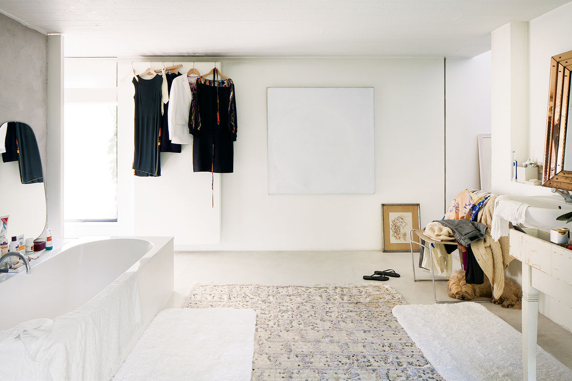 a white bathtub sits in the left corner opposite a white and silver vanity and a gold-framed mirror
