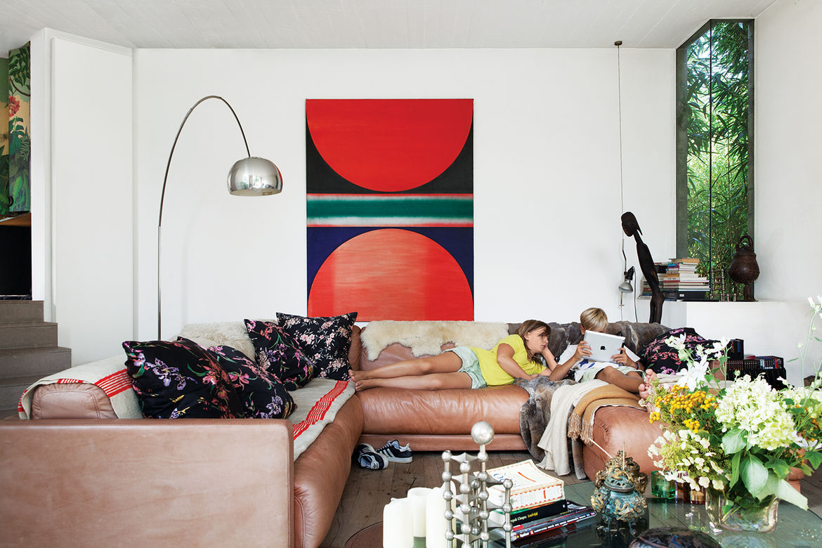 tan couches in a room with white walls and a red and blue painting