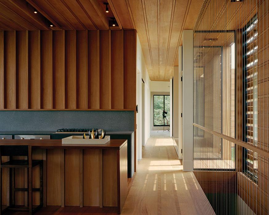 Open kitchen made of mahogany with a volcanic stone backsplash